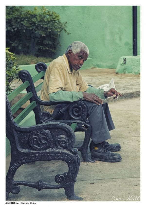 Artistic colour photo print of a man reading the newspaper on a bench in Havana, Cuba.