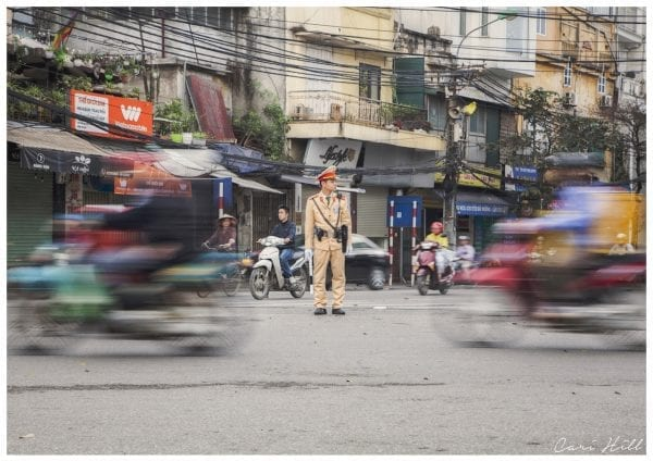 Artistic colour photo print of a street scene in Hanoi, Vietnam depicting movement blur of passing traffic and a still traffic warden in the middle.