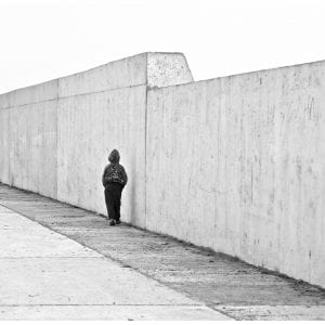 Artistic B&W photo print of a lone boy walking against a wall in Casablanca, Morocco.