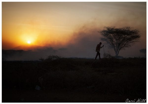 Artistic colour photo print of smoky burning landscape with a silhouette of a Maasai man and a spiky acacia tree and the setting sun.