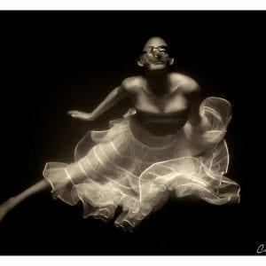 Artistic sepia photo print of a woman underwater blowing bubbles.