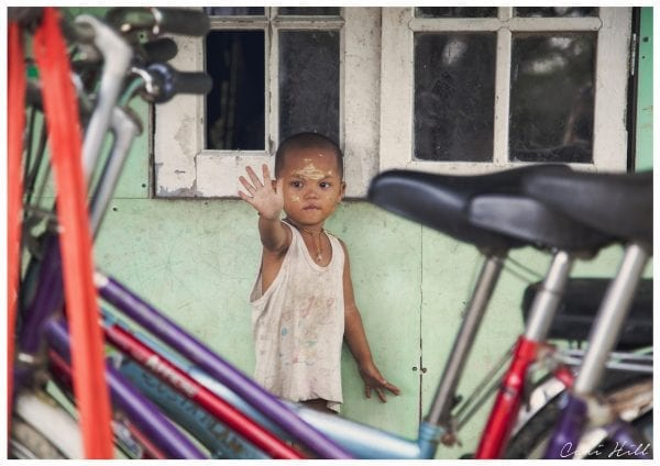 Artistic colour photo print of a child waving framed between bicycles in Myanmar (Burma).