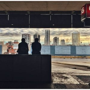 Artistic photo print of a silhouette of two men at Retiro Bus Station in Buenos Aires, Argentina with a dusky cityscape in front of them.