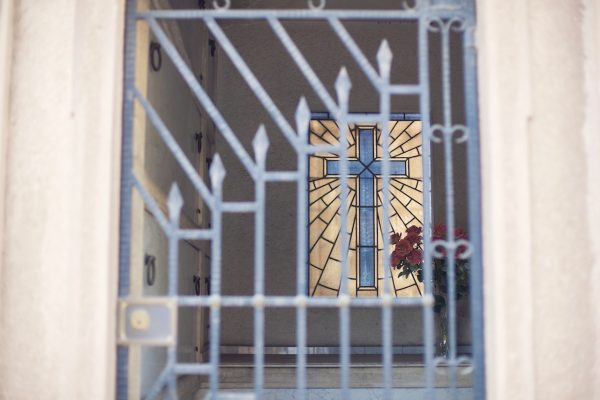Artistic colour photo print of a blue cross in a mausoleum at a cemetery in Santiago, Chile.