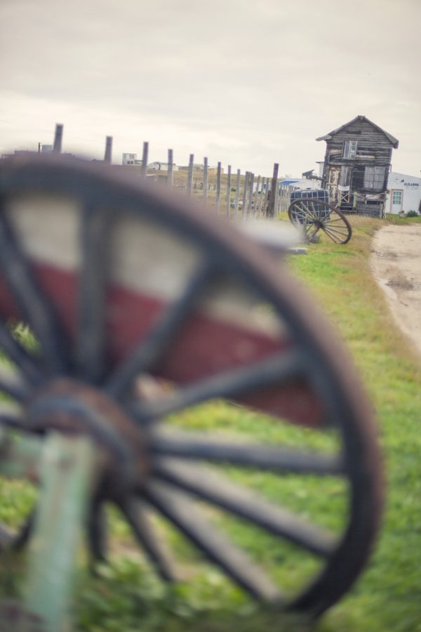 Artistic colour photo print of a little crroked house and an antique wheel in Cabo Polonio, Uruguay.