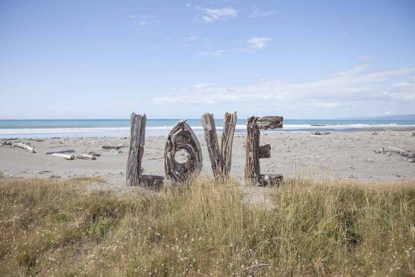 Artistic colour photo print of a human-sized Love sign made of driftwood sitting on Opotiki Beach, New Zealand.