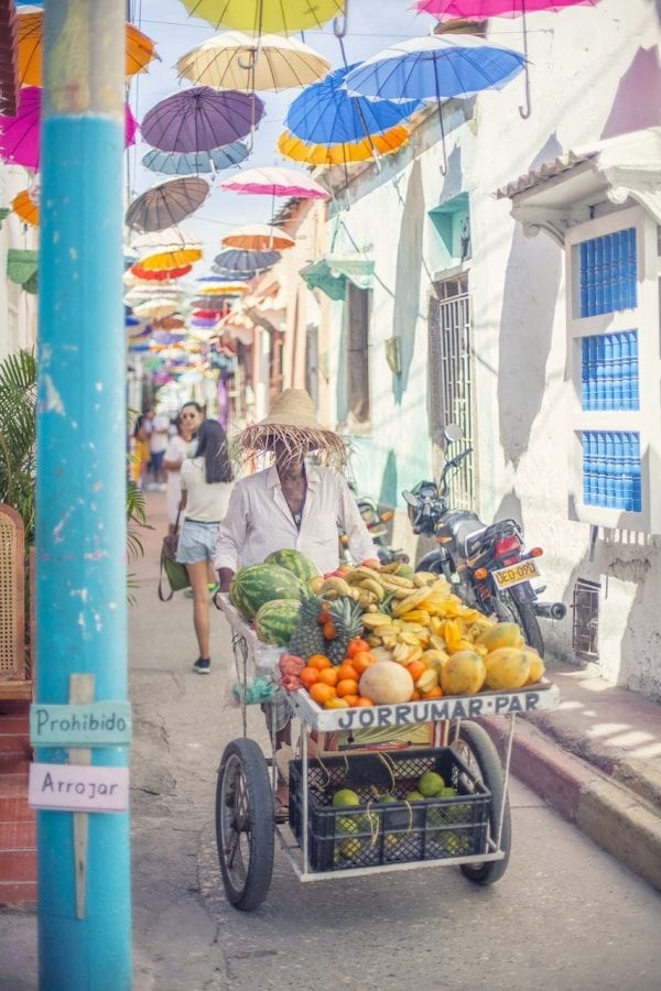 Artistic colour photo print of a fruit seller pushing a cart loaded with fresh tropical fruit in Cartagena, Colombia.