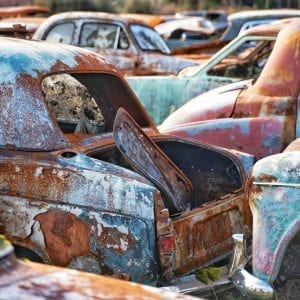 Artistic colour photo of a close-up of multiple rusted vintage cars at a car wreckage called Smash Palace in Horopito, New Zealand.