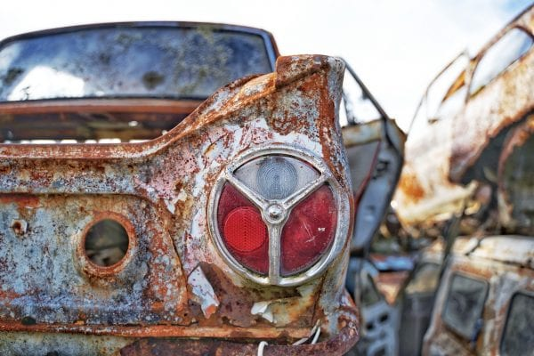 Artistic colour photo of a rusted vintage car headlight at a car wreckage called Smash Palace in Horopito, New Zealand.